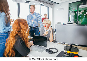 Young attractive blond woman with short hair is making a phone call