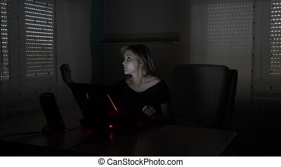 Young attractive blonde business woman sitting at her desk simulating and interaction with a futuristic 3d virtual reality using holographic screen on her laptop