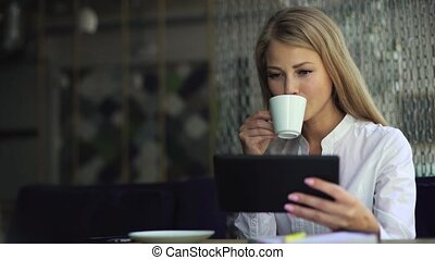Young attractive blonde businesswoman in white shirt at coffee time working on digital tablet while sitting at coffee shop
