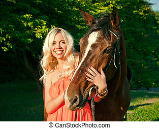 young attractive blonde girl embraces a horse