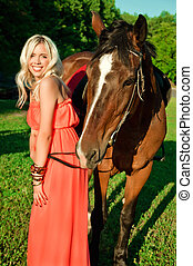 young attractive blonde girl smiling next to a horse