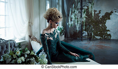 Young attractive blonde woman in a beautiful green dress sitting on the table. Textured background, interior. Luxury hairstyle