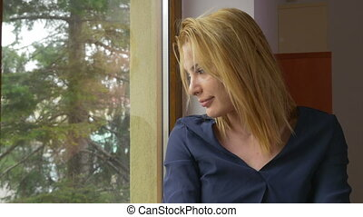 Young attractive bored woman waiting and looking out the...