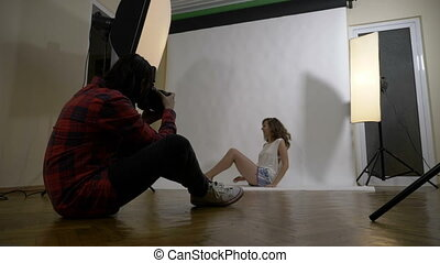 Young attractive boyfriend photographer taking professional pictures of his sexy girlfriend dressed in pajamas in a white studio
