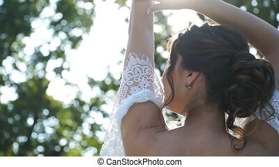 Young attractive bride in white dress with bare back posing on camera in rays of sun. Happy beautiful woman enjoying nature or wedding day outdoor. Concept of marriage. Slow motion Close up.