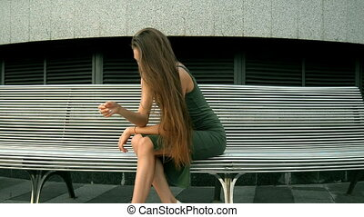 young attractive brunette sitting on the street in a dress