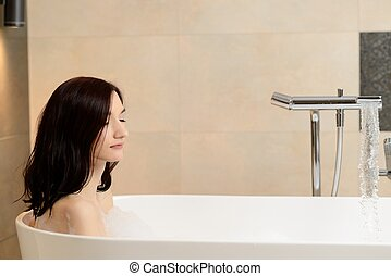 Young attractive brunette taking bath