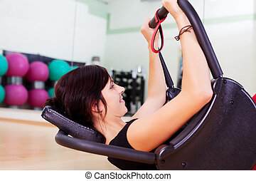 Young attractive brunette woman exercising in gym