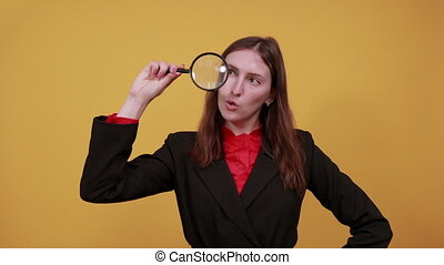 Focused Female Holds A Magnifying Glass In Her Hand And ...