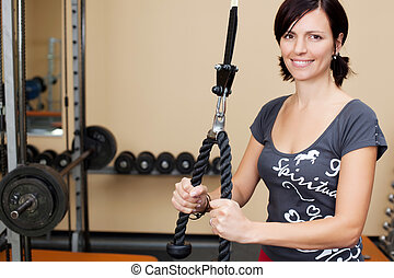 Young attractive brunette woman in the gym