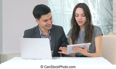 Young attractive business man and woman discussing collating data