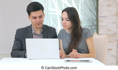 Young attractive business man and woman discussing comparing the data on the laptop