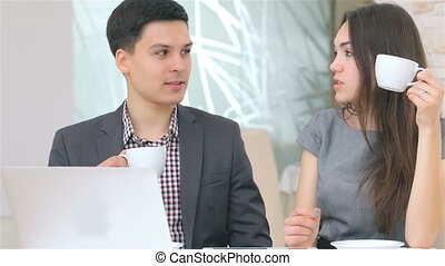 Young attractive business man and woman drink coffee