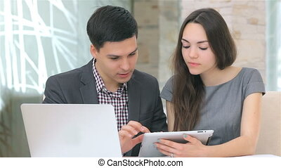 Young attractive business man and woman discussing collating data on the tablet