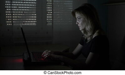 Young attractive business woman sitting at her desk in a dark room typing and chatting with clients on laptop