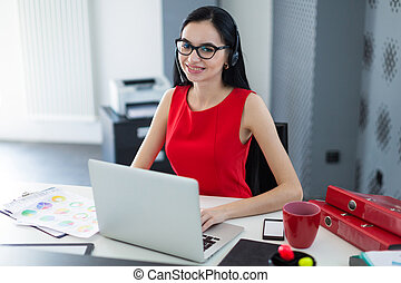 Young attractive businesslady in red dress and glasses sit at th