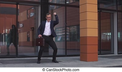 Young attractive Businessman in glasses is dancing near the business center holding a briefcase in his hands. HD