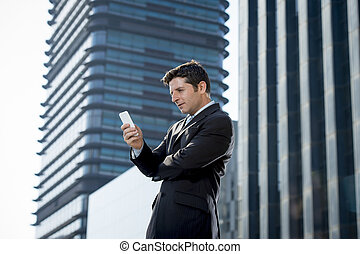 young attractive businessman in suit and necktie looking text message at mobile phone outdoors