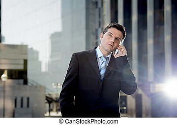 young attractive businessman in suit and tie talking on mobile phone happy outdoors