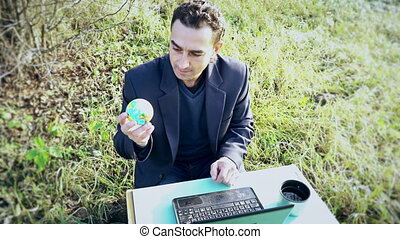Young Attractive Businessman in suit with laptop computer sitting on green meadow outside, office outdoors, big boss holding globe earth and decide human destiny, god hands, concept