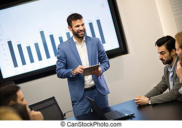 Young attractive businessman showing presentation to his colleagues