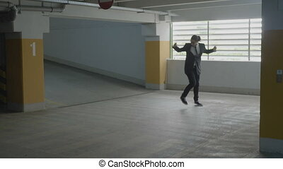 Young attractive businessman wearing formal suit jumping and funny dancing in a underground parking lot on his way to the car