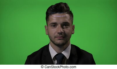 Young attractive businessman with code on face working as a computer programmer on green screen background