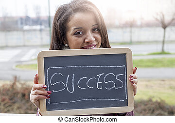 young attractive businesswoman shows a blackboard marked with business concepts