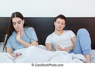 Young attractive caucasian couple with smartphones in pajamas in their bed searching or browsing over internet and texting in chat with other people, cheating over messages, checking each other phones