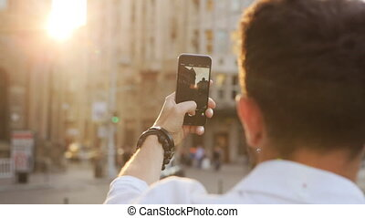 Young attractive caucasian guy taking picture by using his smartphone.