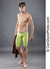 Young attractive caucasian man swimmer with goggles and towel isolated over Gray background