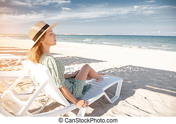 Young attractive caucasian woman in a green dress and a straw sits resting on a lounger under a wooden umbrella on a sandy beach of the seashore or ocean.