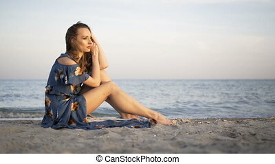 Young attractive cheerful girl sitting on the beach