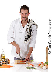 Young attractive chef caucasian male with uniform, cutting carrots for preparing a tenderloin piece with fresh vegetables and herbs. Studio shot. White background.