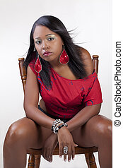 Young attractive confident black woman on chair