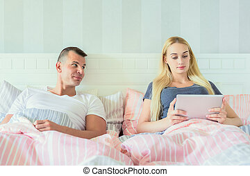 Young attractive couple in bed, using digital tablet.