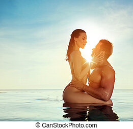 Young, attractive couple relaxing in a warm, tropical pool