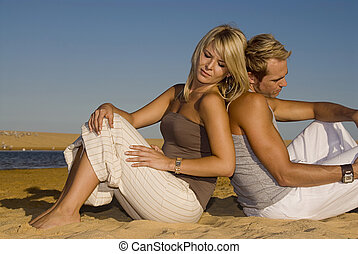 Young attractive couple sitting on the beach