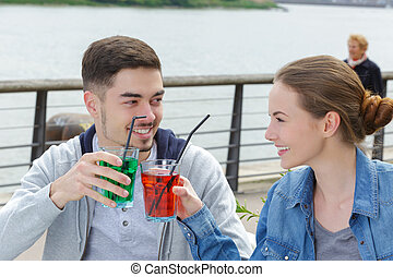 young attractive couple toasting with cordials at bar terrace