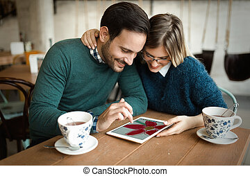 Young attractive couple using tablet in coffee shop