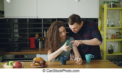young attractive curly happy caucasian woman is sitting in kitchen texting someone via smartphone, her husband comes and she shows something funny in phone