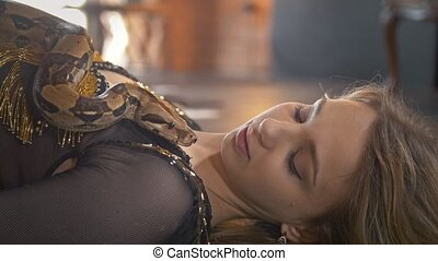 Young attractive dancer lying with python in a studio, close...