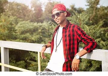 Young attractive dark skinned guy with trees on background