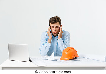 young attractive engineer man feeling tired at work place