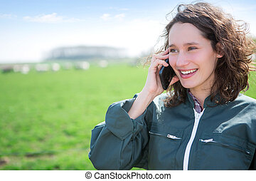 Young attractive farmer in a field using mobile phone - View...