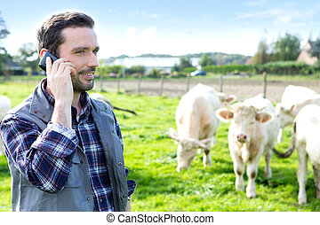 Young attractive farmer using mobile phone in a field - View...