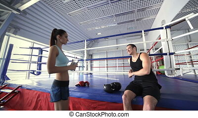 Young attractive female athlete goes to her fitness instructor