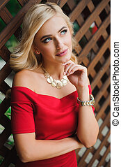 Young attractive female blonde woman in red dress sitting on chair