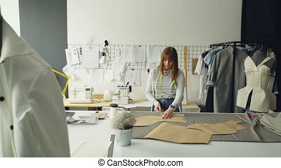 Young attractive female designer is checking her paper templates with measuring tape. Professional creative clothing designing concept. Studio is light and modern.