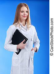 young attractive female doctor is standing with the clipboard an